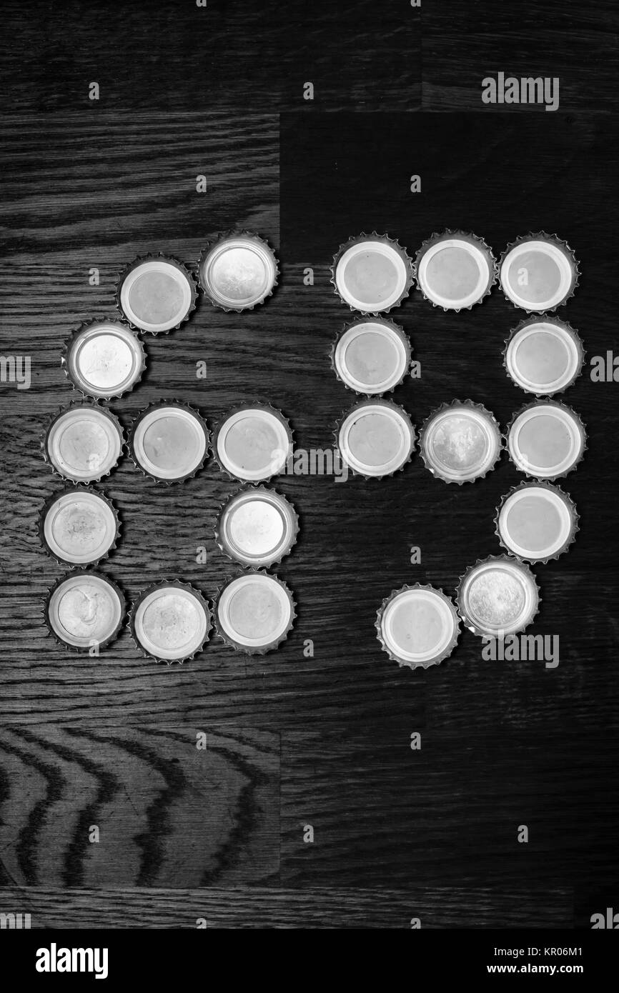 The number 69 on a wooden table laid out of beer caps. Black and white. - Stock Image