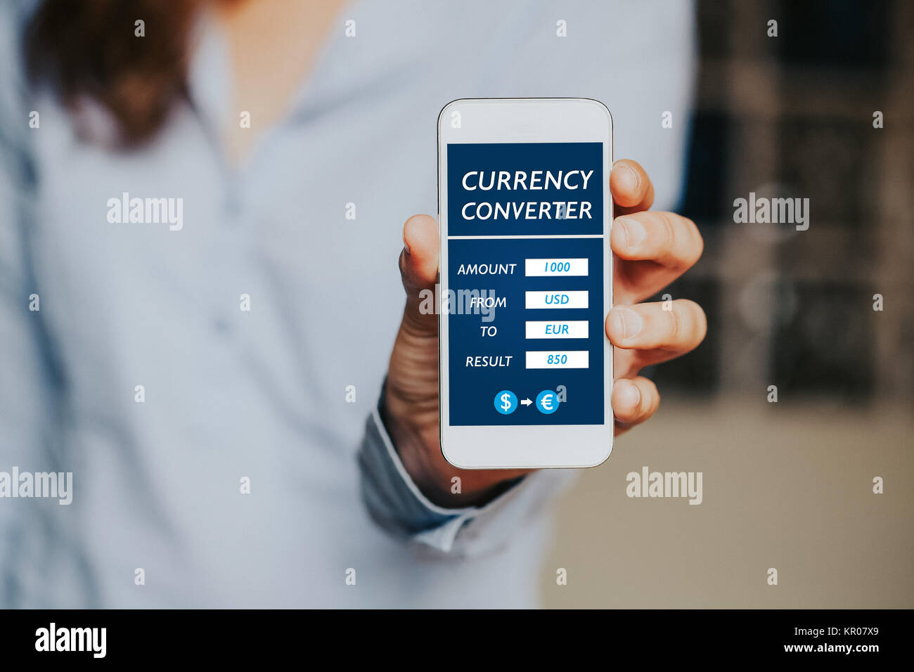 Woman holding a mobile phone with a currency converter app in the