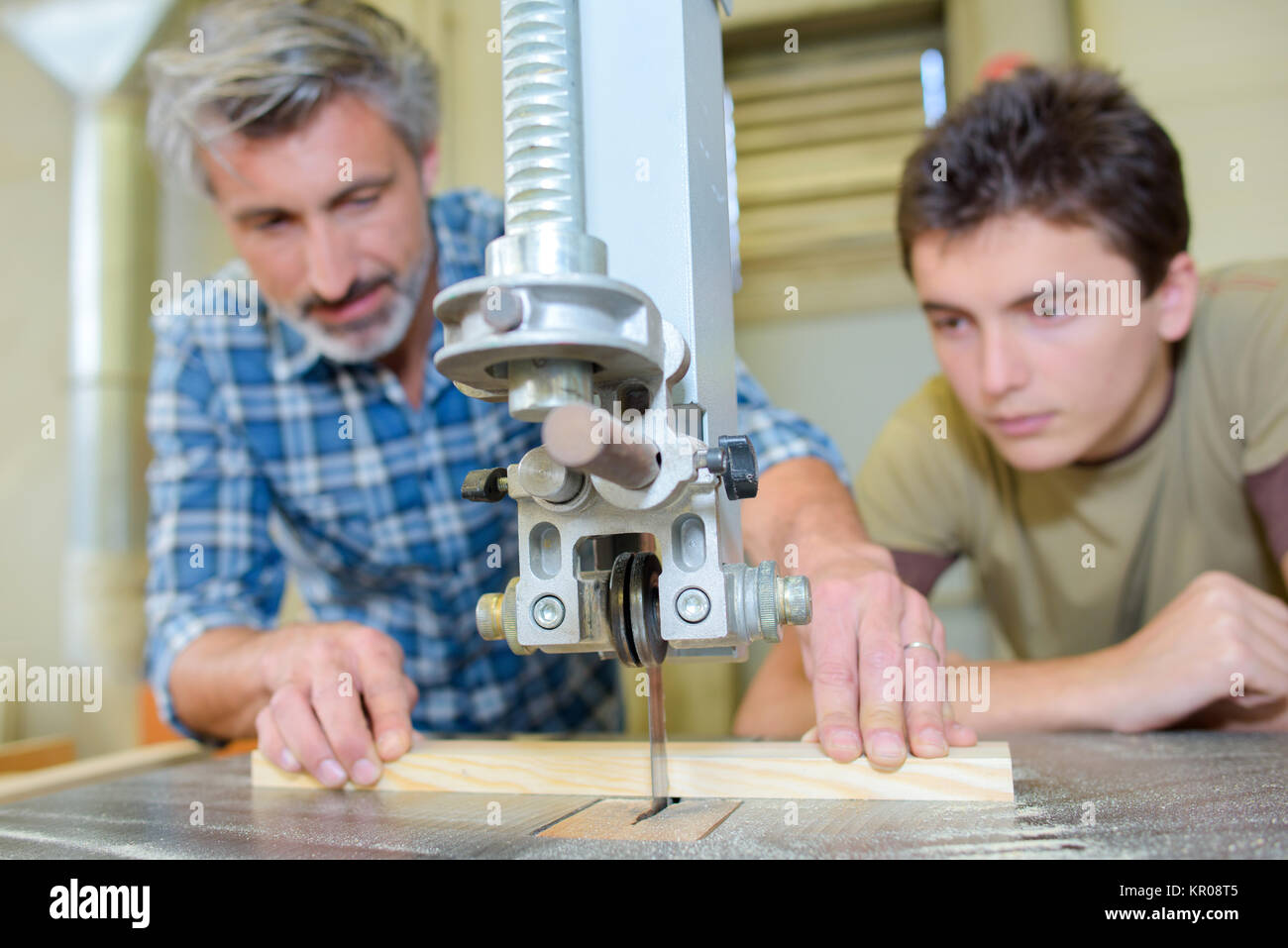 Carpenter teaching apprentice to use a bench saw - Stock Image