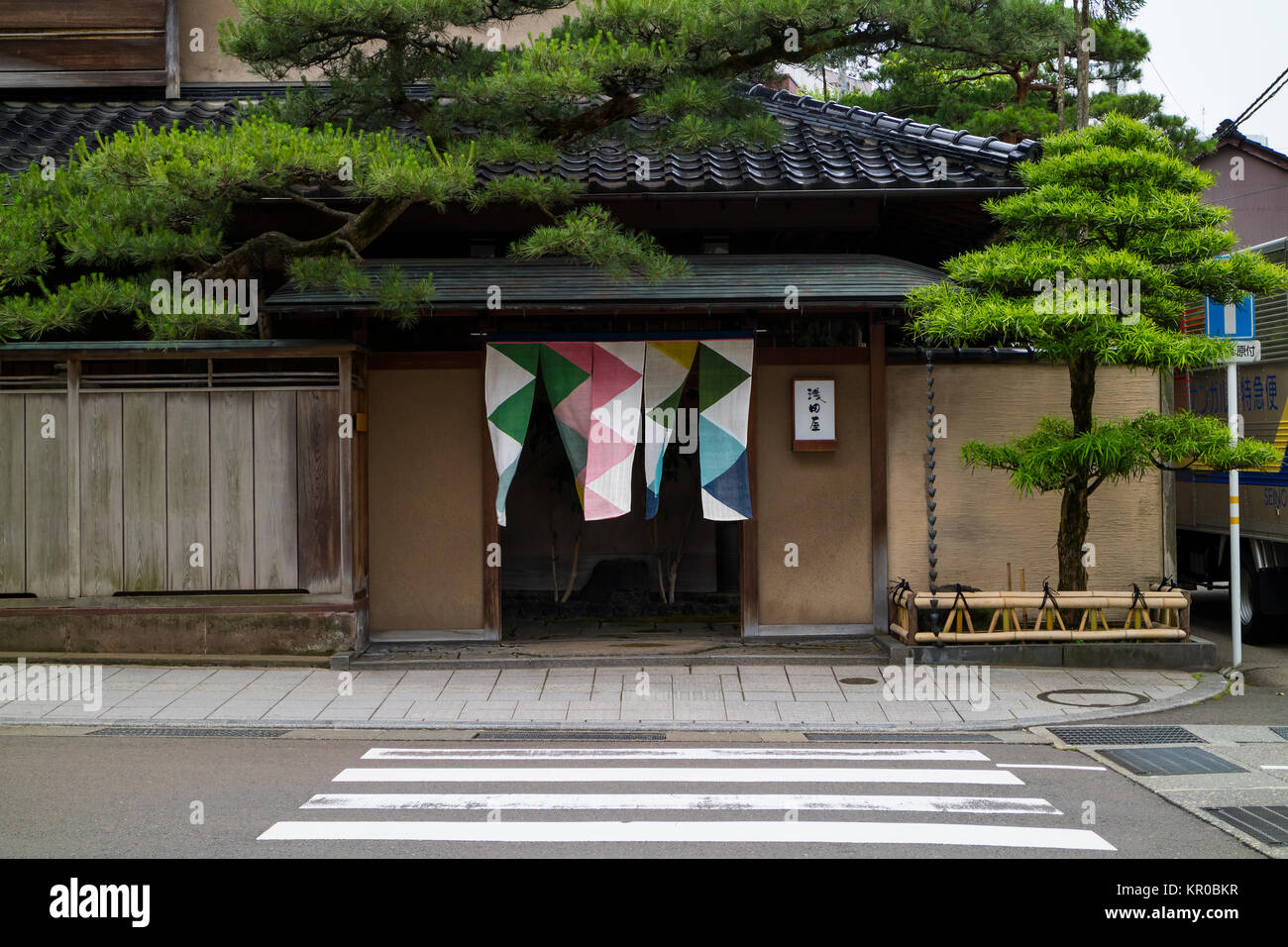 Kanazawa - Japan, June 10, 2017: Entrance to a restaurant with colorful curtains and trees in shape - Stock Image