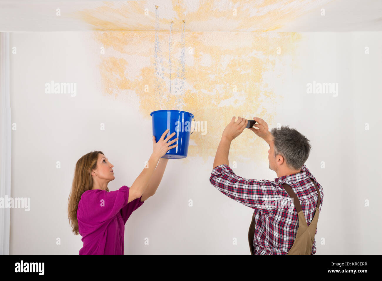 Man Photographing While Woman Collecting Water From Ceiling - Stock Image