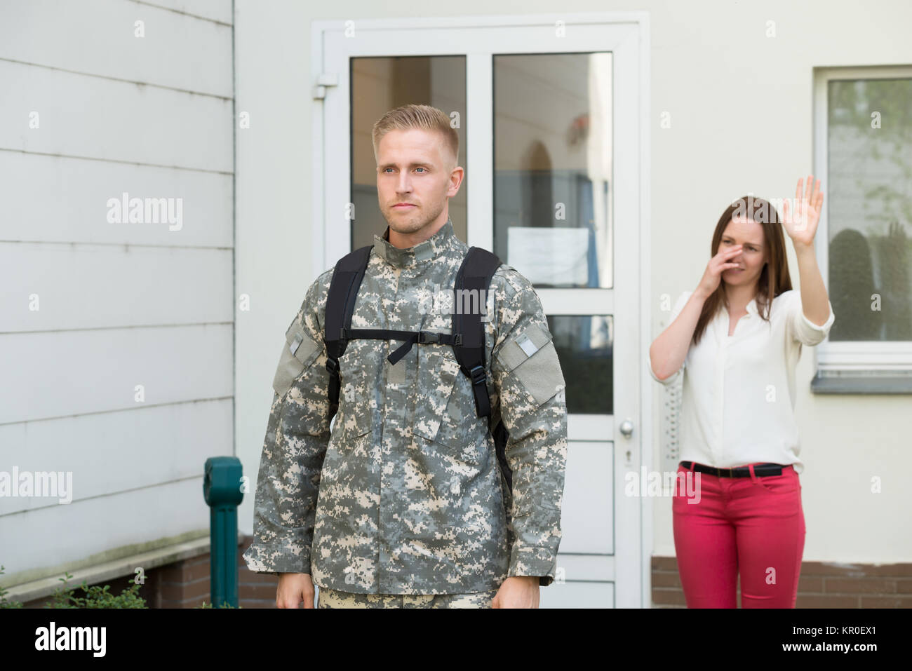 Unhappy Wife Waving Goodbye To Male Soldier - Stock Image