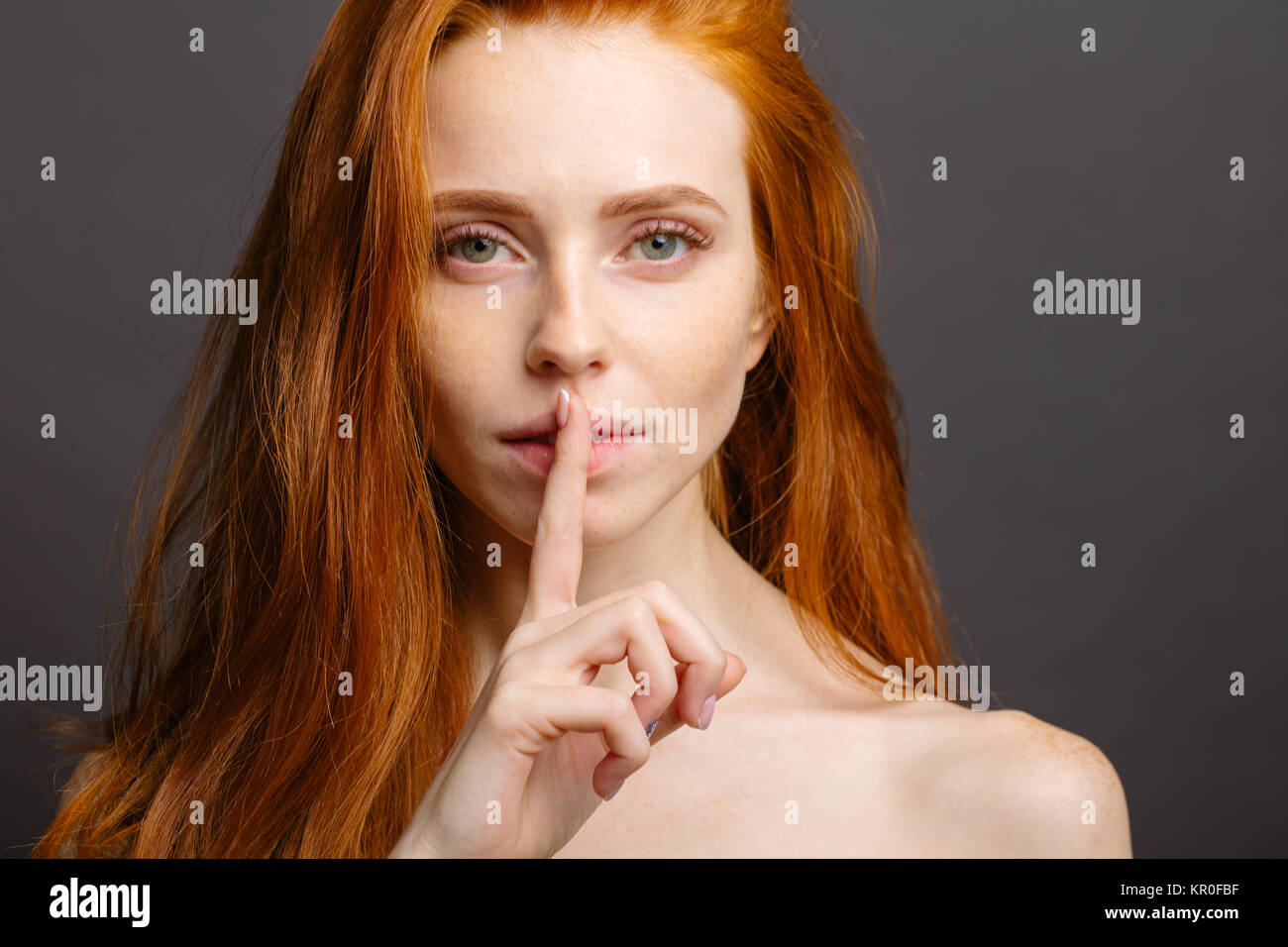girl holding index finger at her lips, saying 'shh' - Stock Image