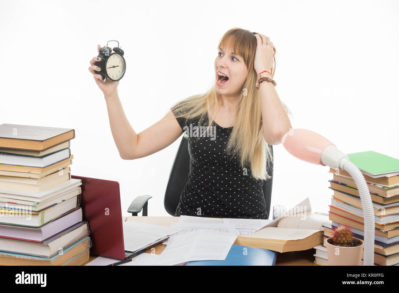 A student with an alarm clock in hands understand that slept exam and screaming looking at his watch - Stock Image