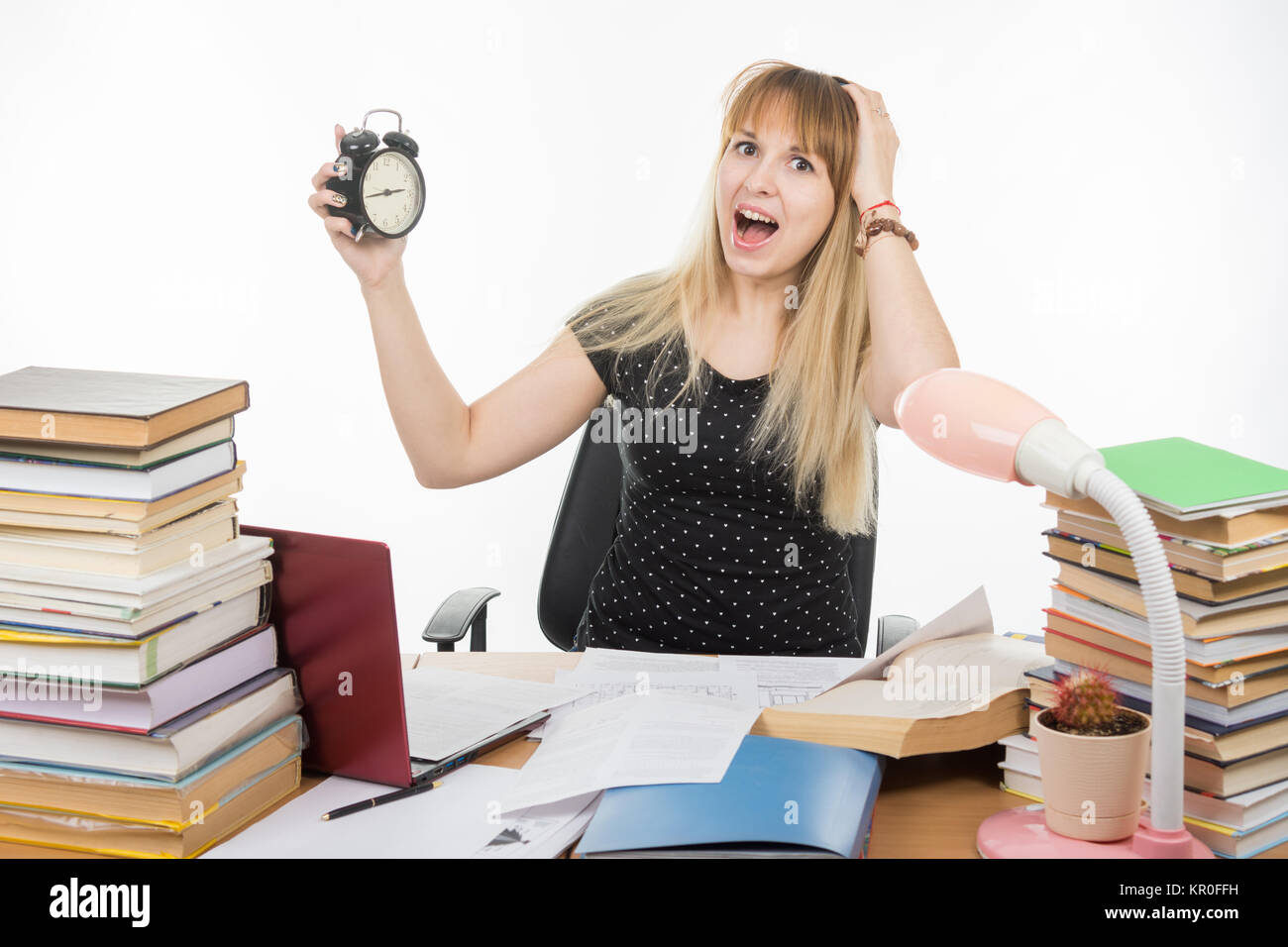 A student with an alarm clock in hands understand that slept exam - Stock Image