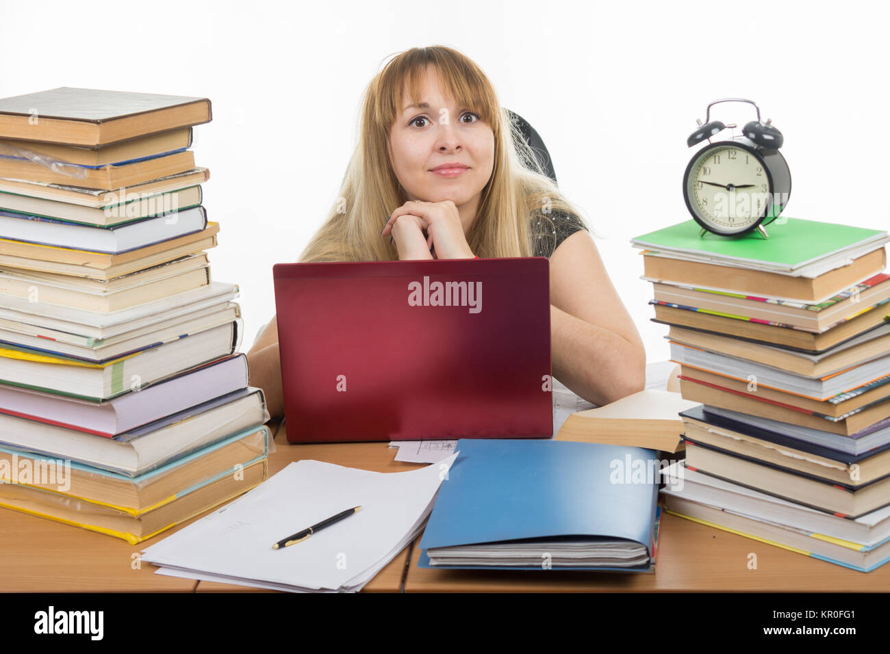 Disheveled student sitting at the table and looking at the frame - Stock Image