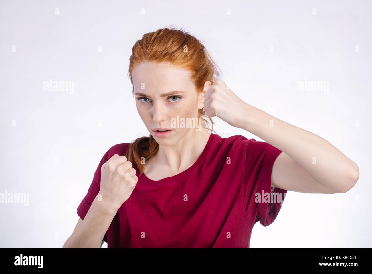angry woman standing with raised knuckles on white background - Stock Image