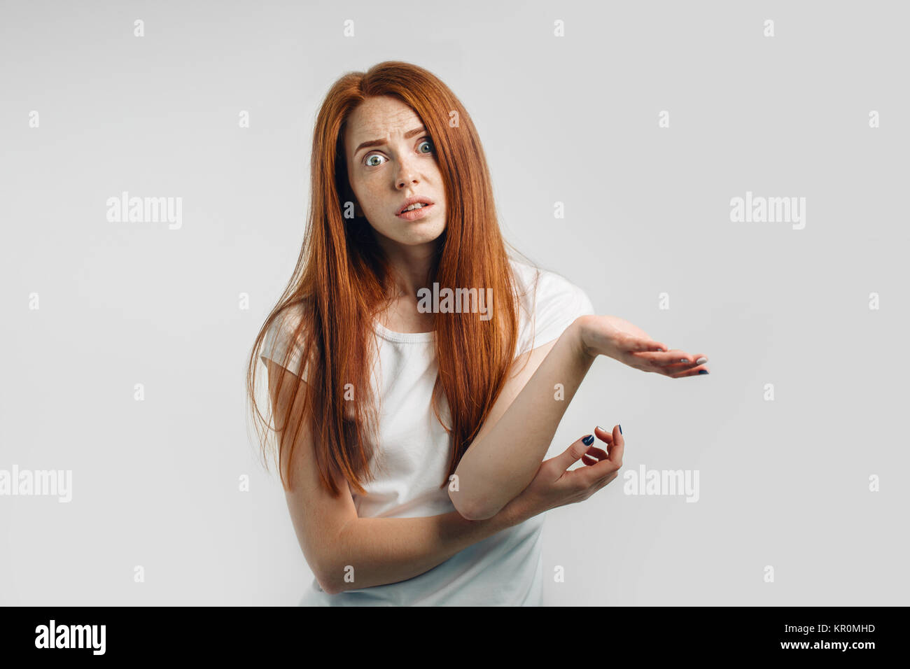 Puzzled and clueless young redhead woman with arms out - Stock Image
