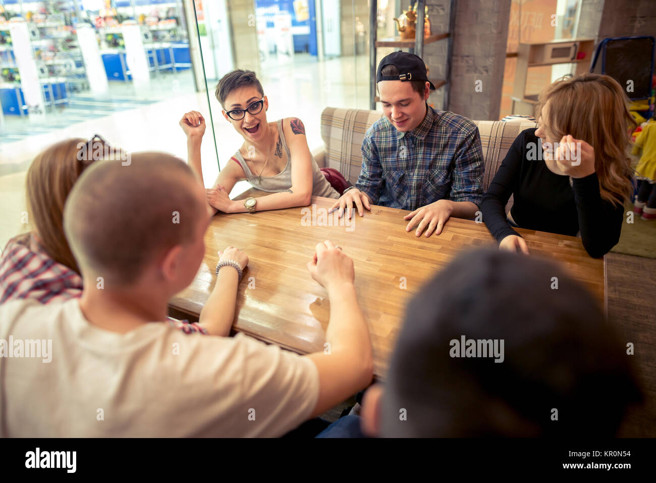Group of students sitting in a cafe bar looking at each other - Stock Image