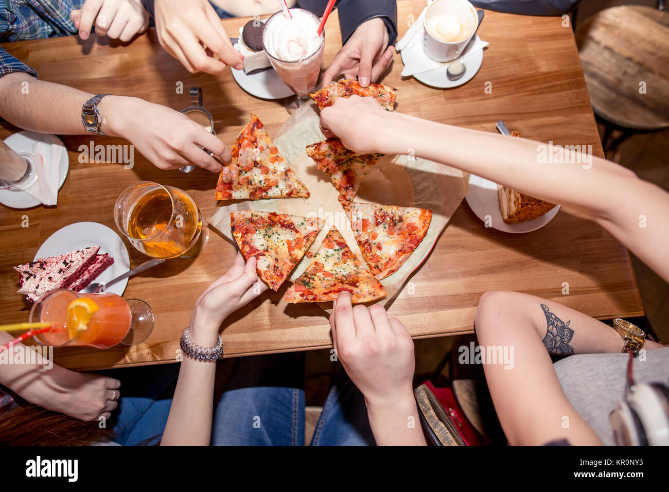 Friends eating pizza at home party, closeup - Stock Image