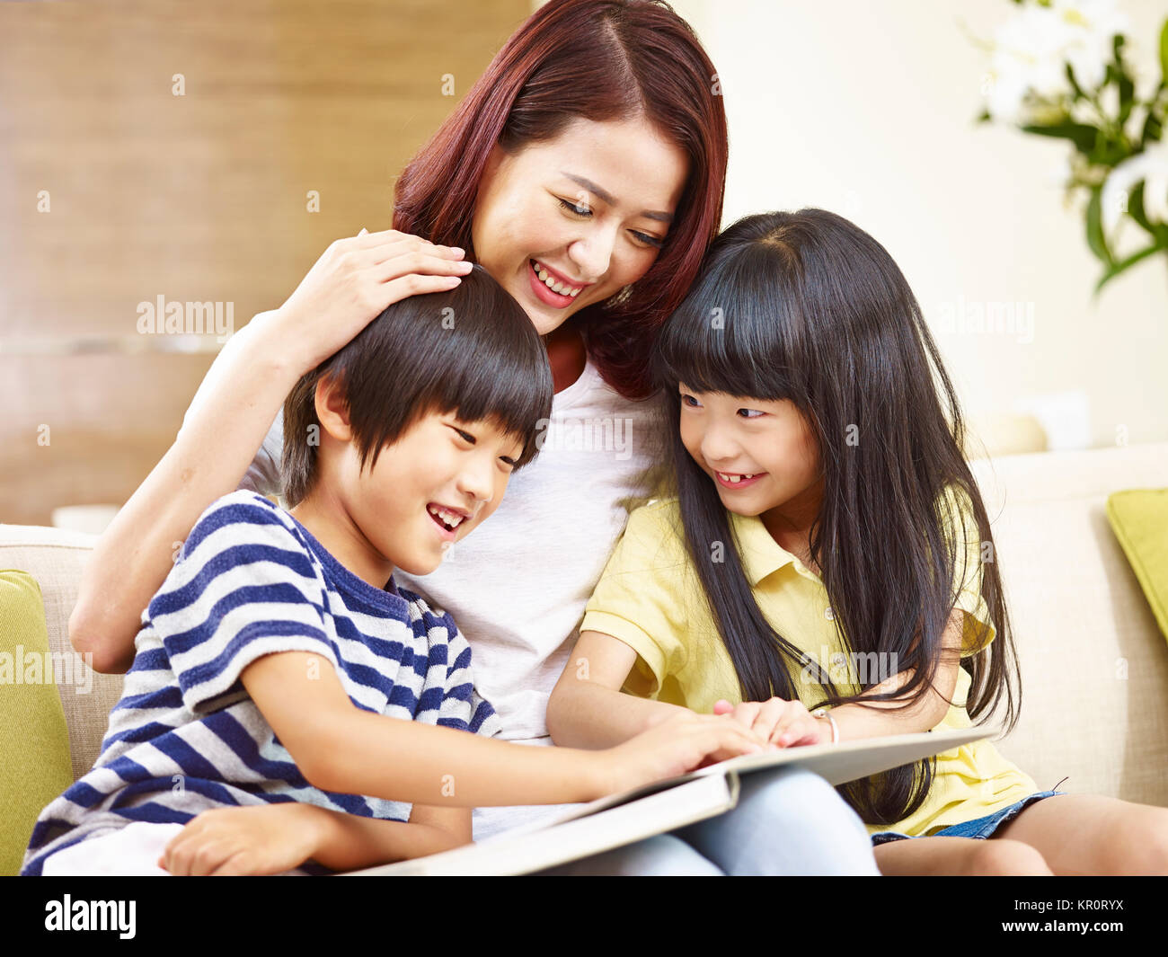 young asian mother sitting on couch at home reading story to two little children. - Stock Image
