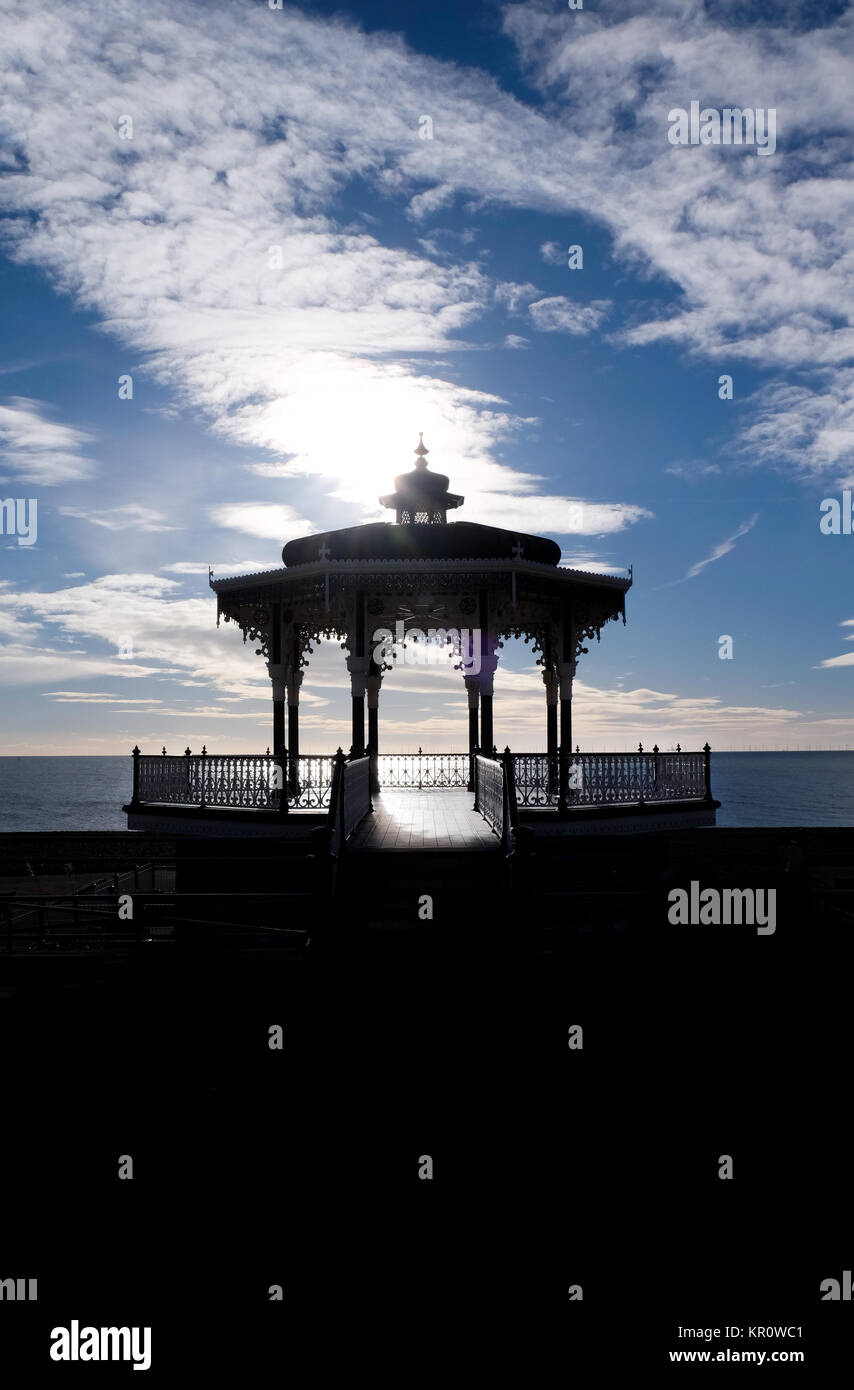 Brighton victorian bandstand silhoutted black by sun behind it, dramatic blue and white cloudy sky, black forground, Stock Photo