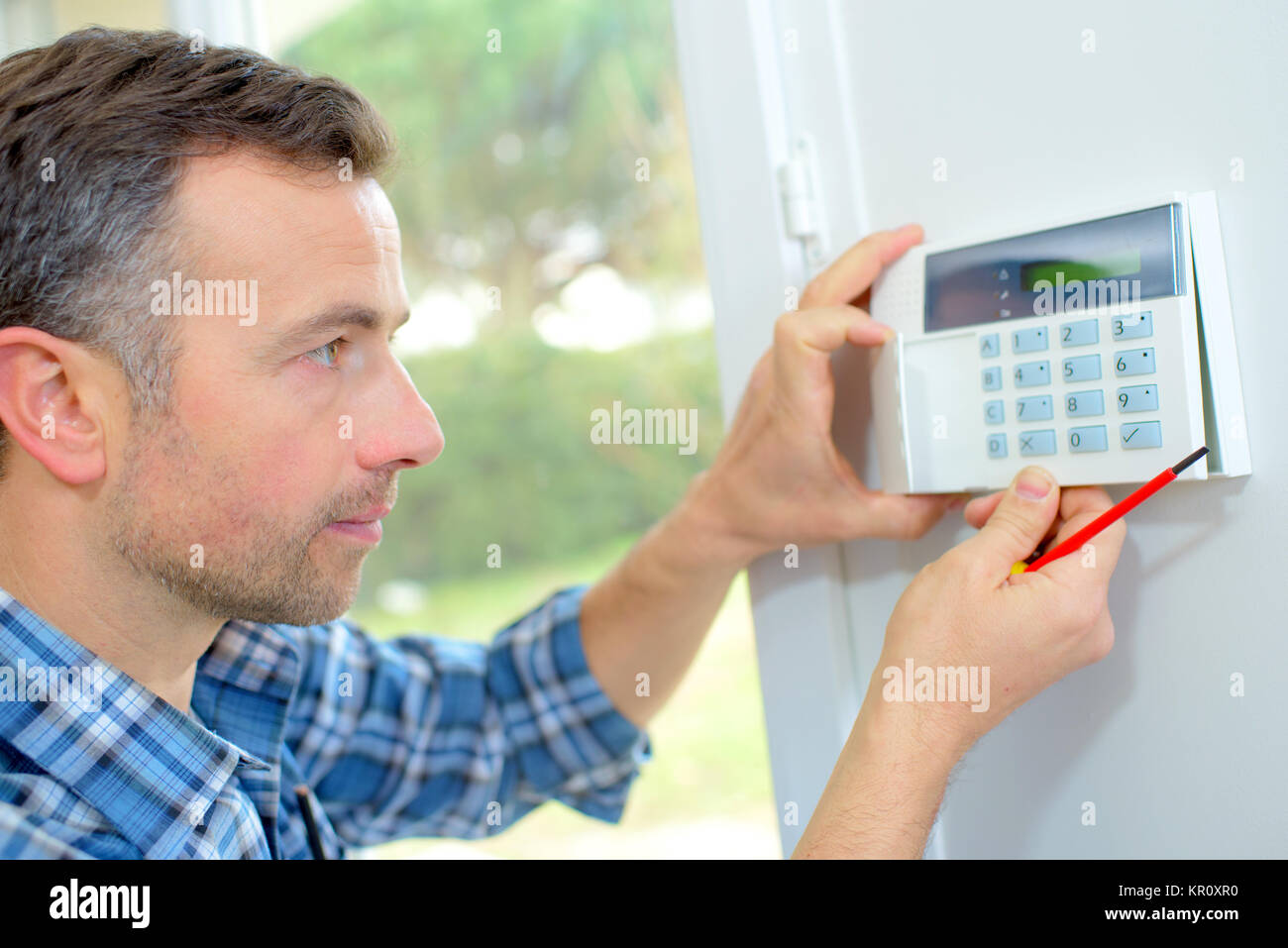 Electrician fitting an intrusion alarm - Stock Image