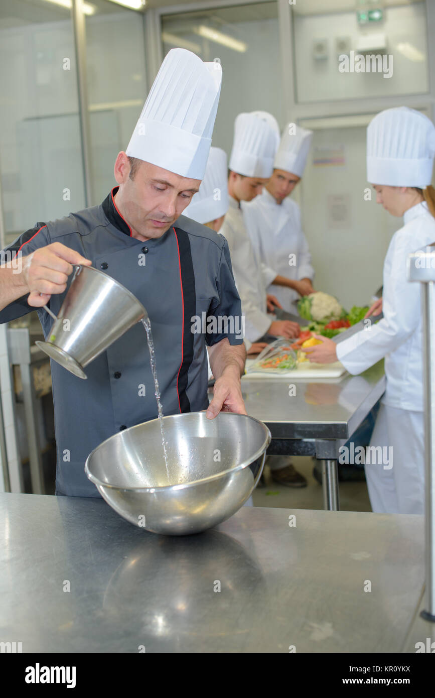 Chef pouring into stainless steel bowl - Stock Image