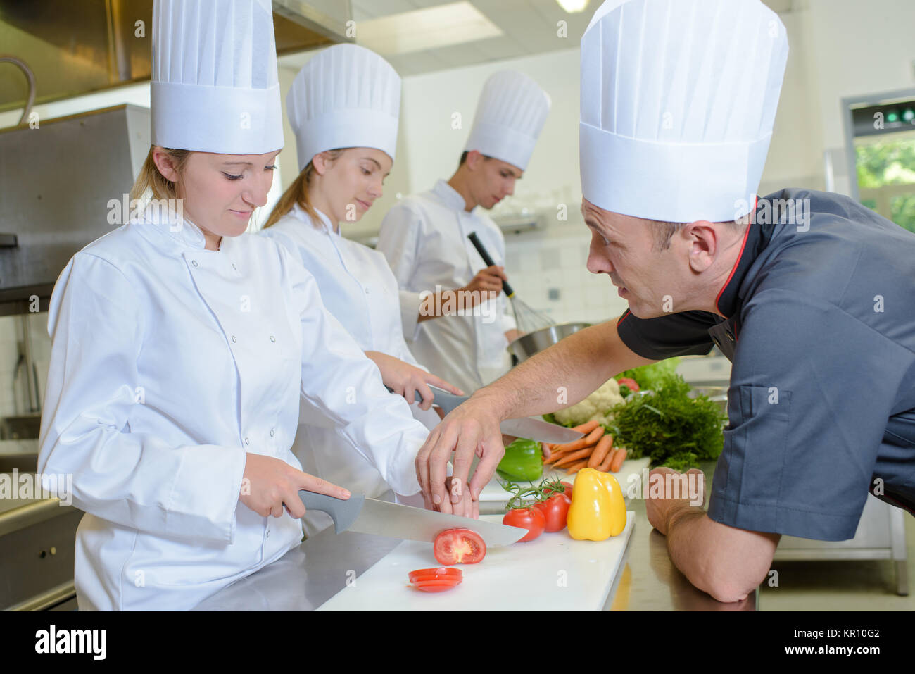 Chef guiding trainee - Stock Image