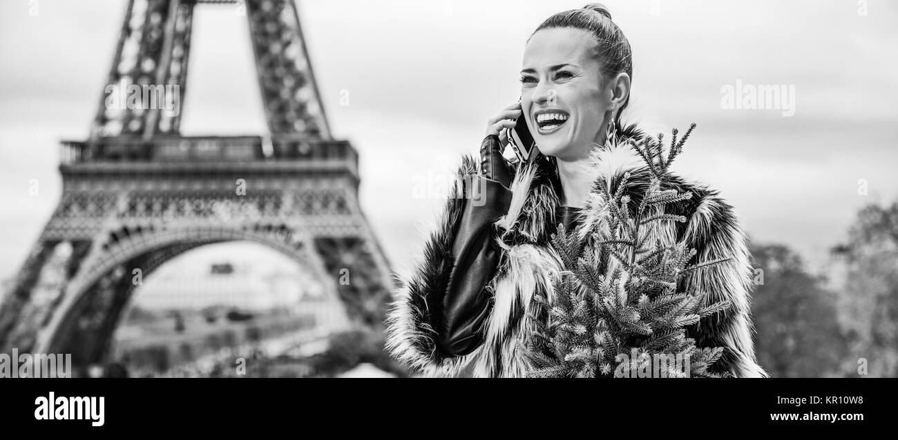 The Party Season in Paris. Portrait of happy modern fashion-monger with Christmas tree in fur coat in the front - Stock Image