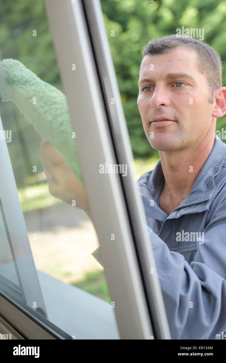 cleaning a glass window - Stock Image