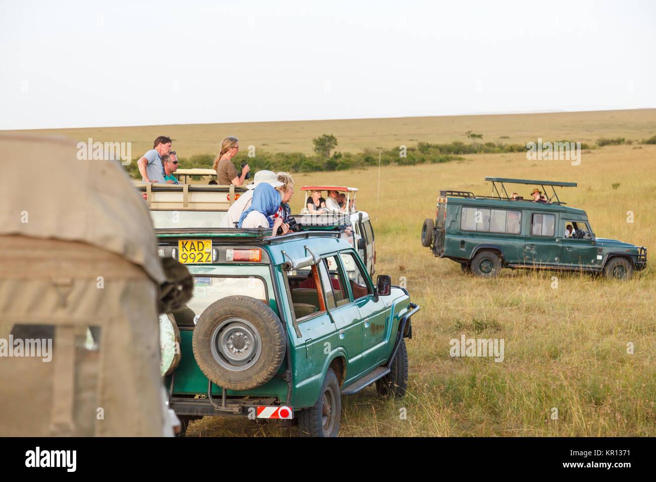Tourists in safari vehicles on the savannah of the Masai Mara, Kenya - Stock Image