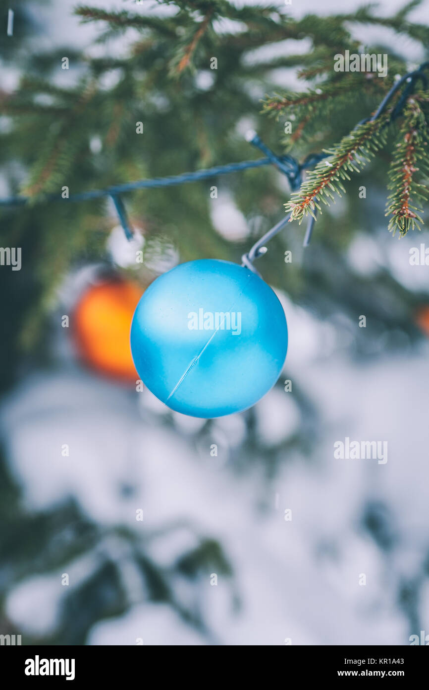Close-up of baubles and fairy lights hanging on a Christmas tree Stock Photo