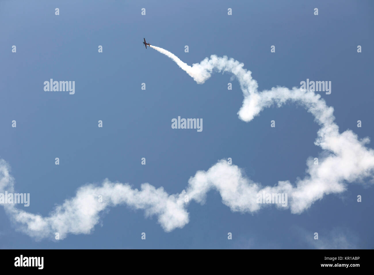 Aerobatic plane with a white smoke trail in sky. - Stock Image