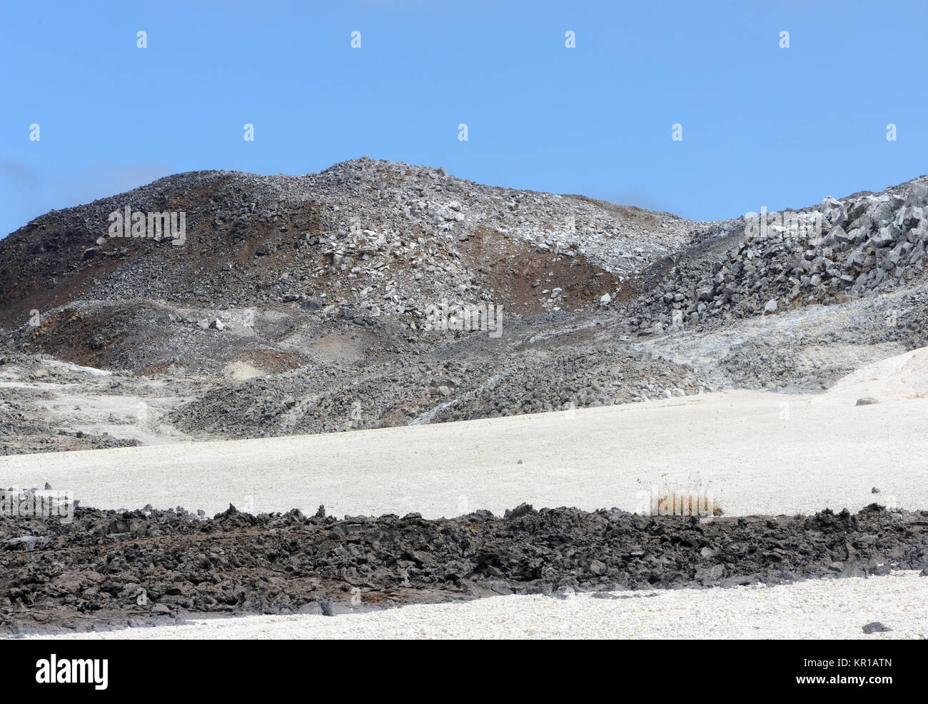 Eroded sulphur minerals below active fumaroles look like white sand and black lava rocks within the caldera of the - Stock Image