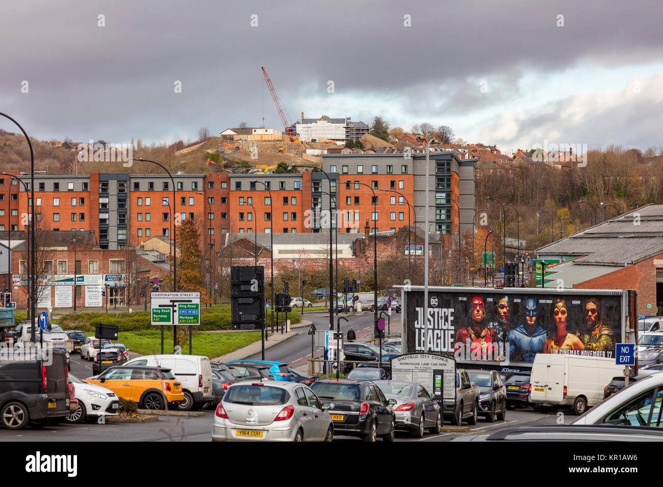 Development on a hill above Sheffield, a large Justice League poster on a hording in the foreground, Sheffield, - Stock Image