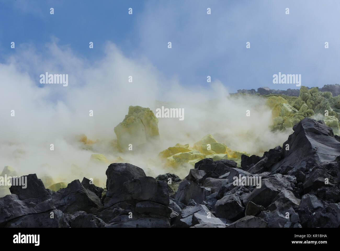 Clouds of sulphuric acid laden steam billow from active fumaroles and deposits of sulphur within the caldera of - Stock Image