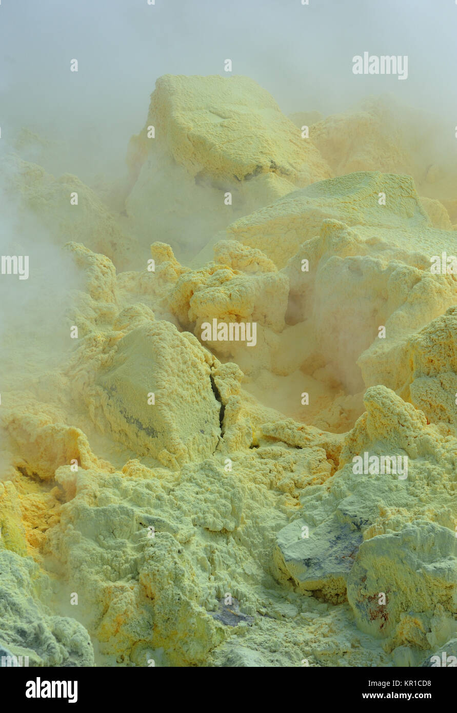 Clouds of sulphuric acid laden steam billow from active fumaroles and deposit sulphur on lava rocks within the caldera - Stock Image