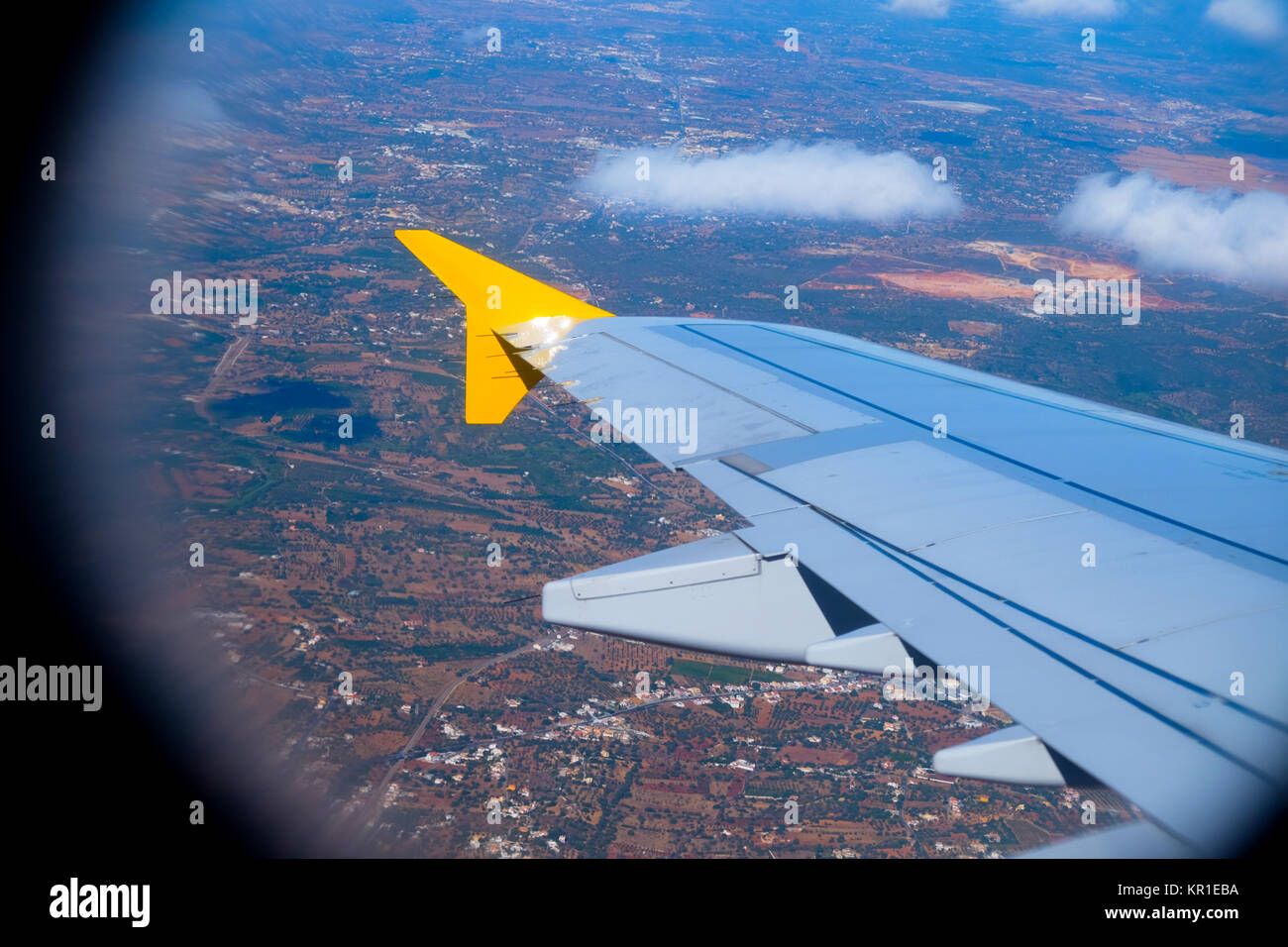 View point from inside and airoplane looking out over the left aircraft wing, in the background is the Algarve, - Stock Image
