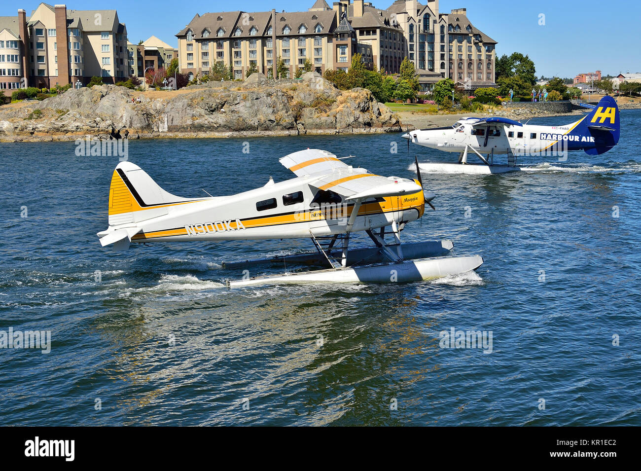 Two commuter aircraft taxi by on another at the busy Victoria harbour on Vancouver Island British Columbia, Canada. - Stock Image