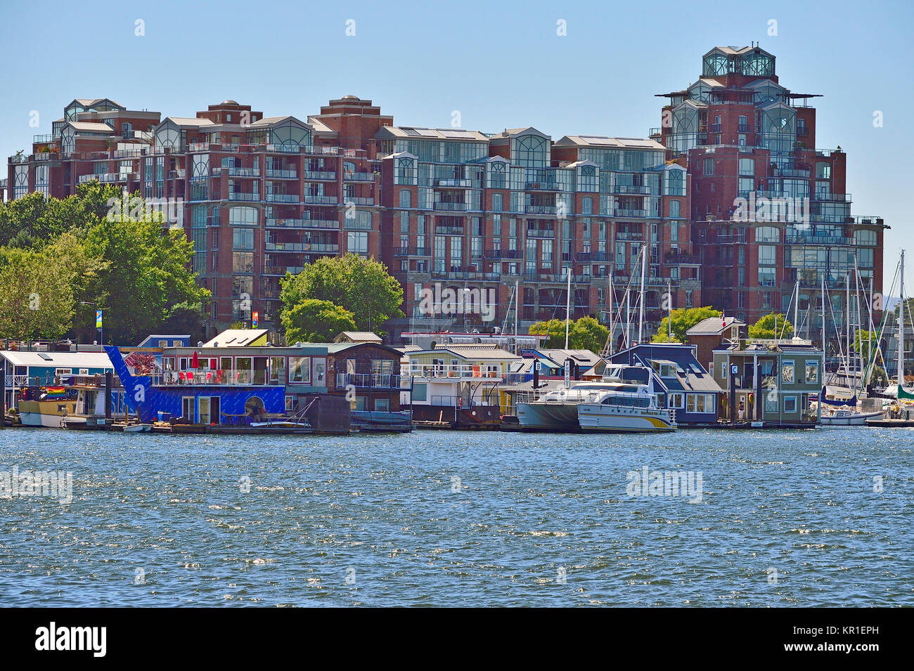 A group of floating homes thed up to a dock in front of a large condo complex at the Victoria harbour on Vancouver - Stock Image