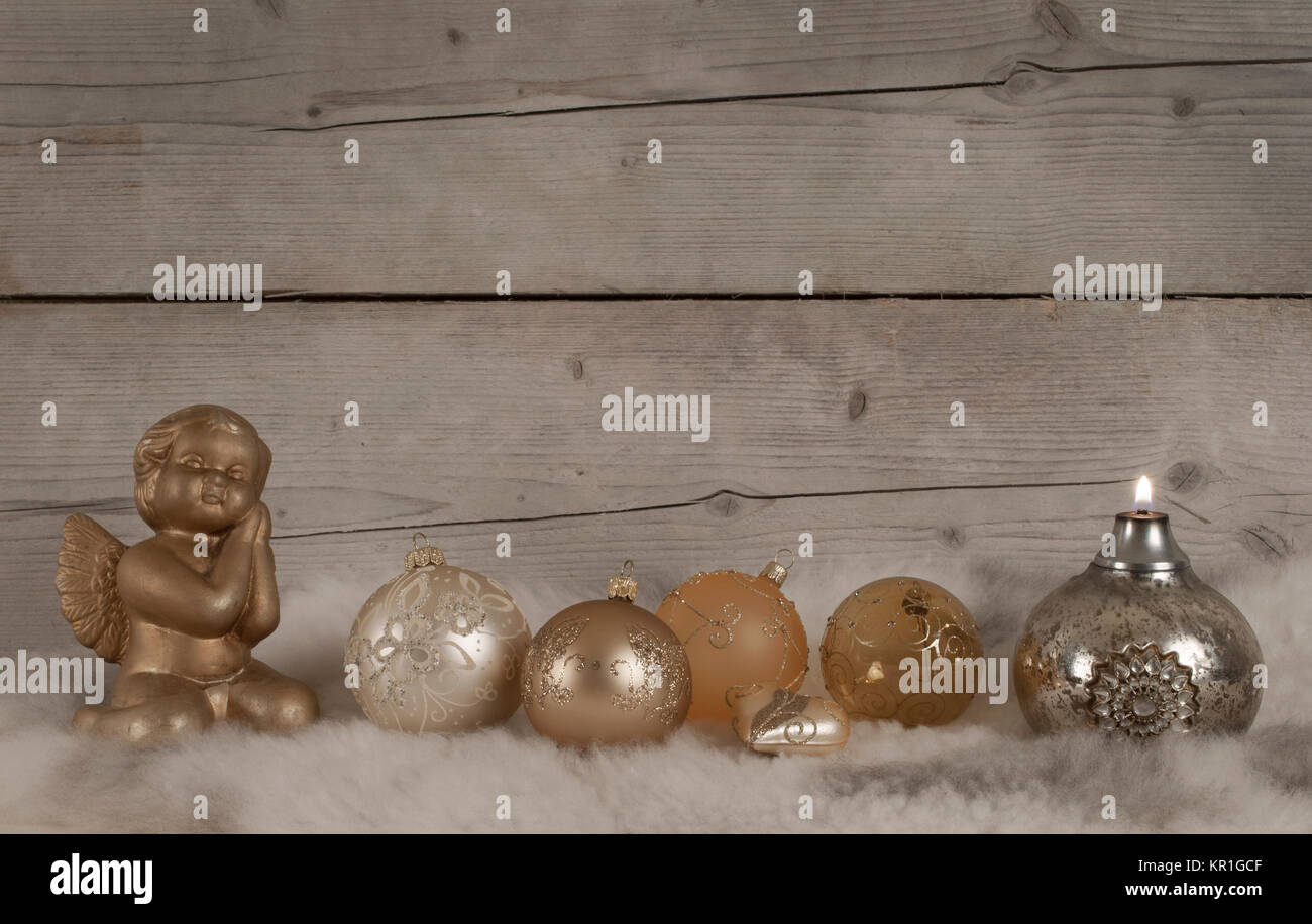beautiful bronze and golden glass christmas baubles and candle and angel, on sheepskin and weathered wooden background - Stock Image