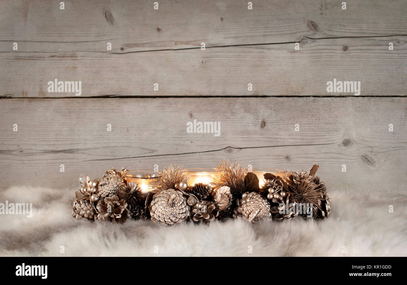 classic golden Christmas tealight holder with burning candles, on sheepskin and weathered wooden background - Stock Image