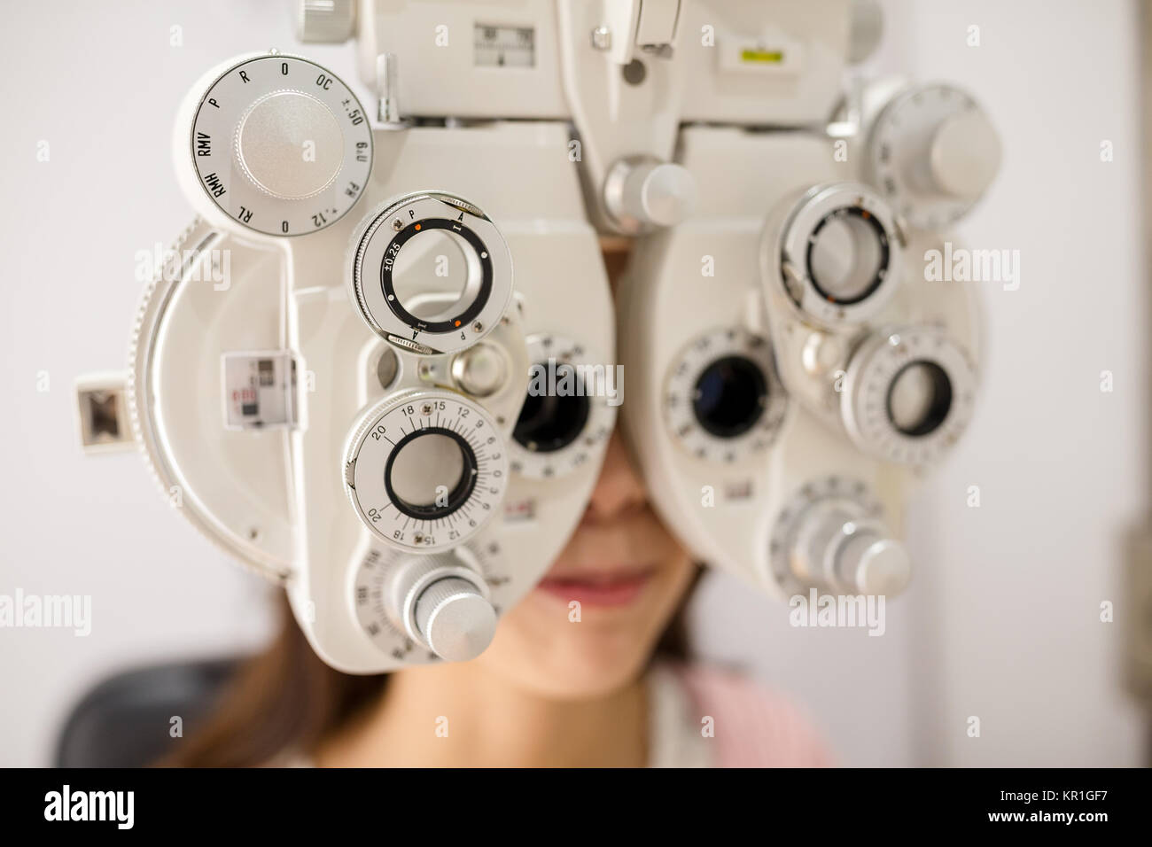 Eyesight measurement to a young woman with a optical phoropter - Stock Image
