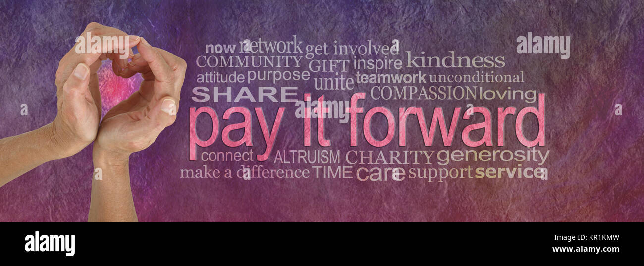 Campaign banner with female hands making a heart shape on left with a PAY IT FORWARD word cloud beside on a rustic - Stock Image