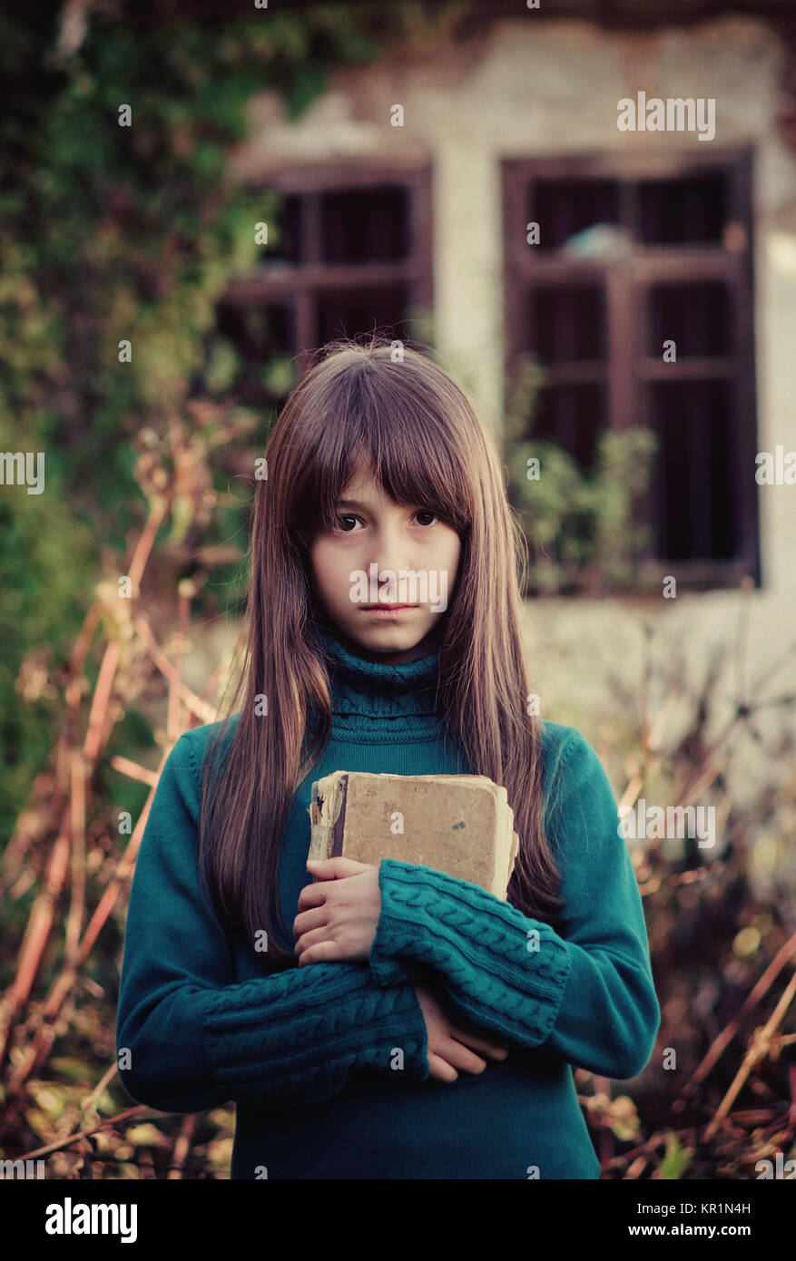 Conceptual portrait of a young girl in front of a desolated house, holding an old book. - Stock Image