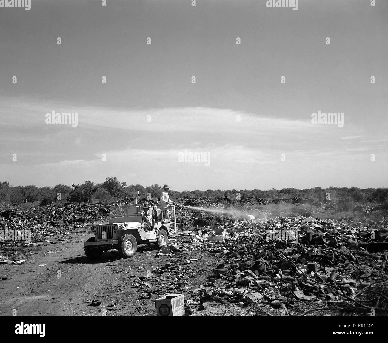 Man standing in the back of a jeep spraying a fly-breeding city dump in Edinburg, Texas, 1946. Flies can transmit - Stock Image