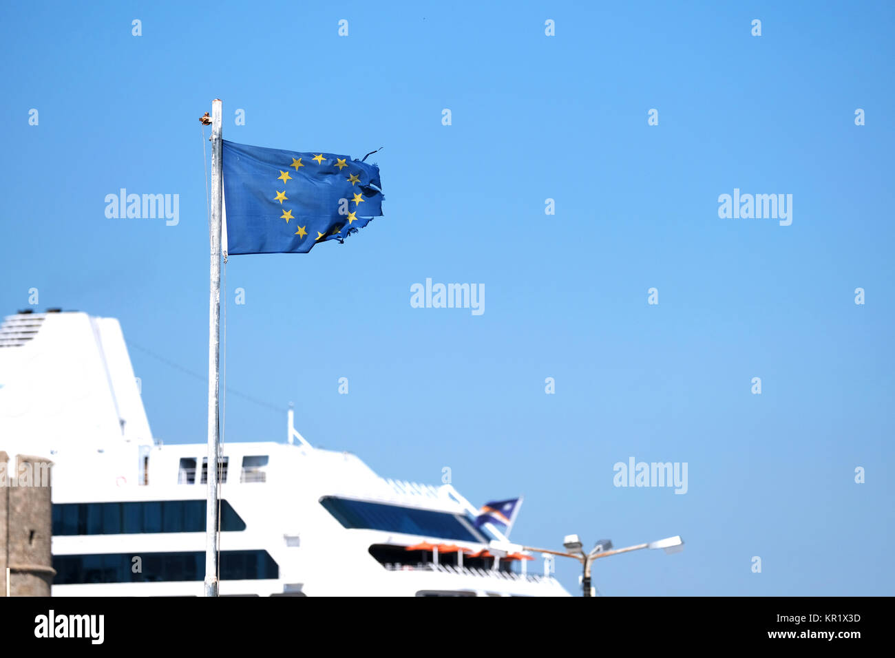 A ragged, torn, sorry looking and battered flag of the European Union flying in a strong wind on the island of Rhodes, - Stock Image