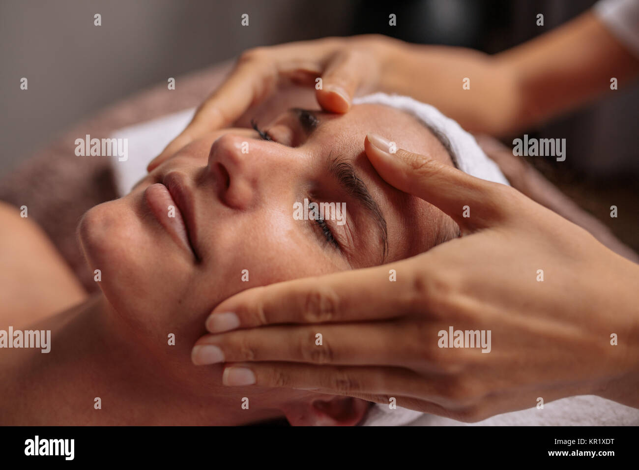 Close up of a woman having facial beauty treatment at spa salon. Beautiful young woman getting a face massage. - Stock Image