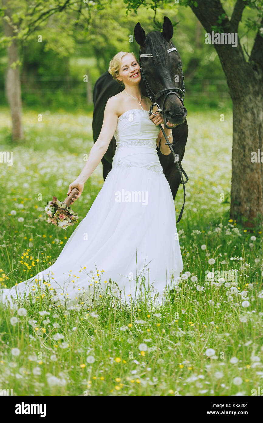 The bride in white wedding dress standing outdoors in a flowering ...