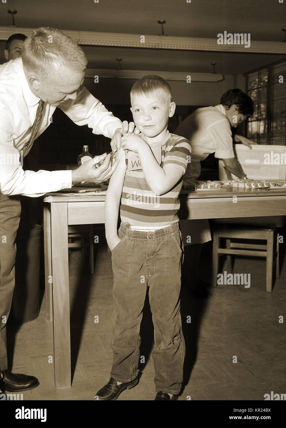 This 1962 image depicts a schoolboy receiving a measles vaccination. As part of the national immunization effort, - Stock Image
