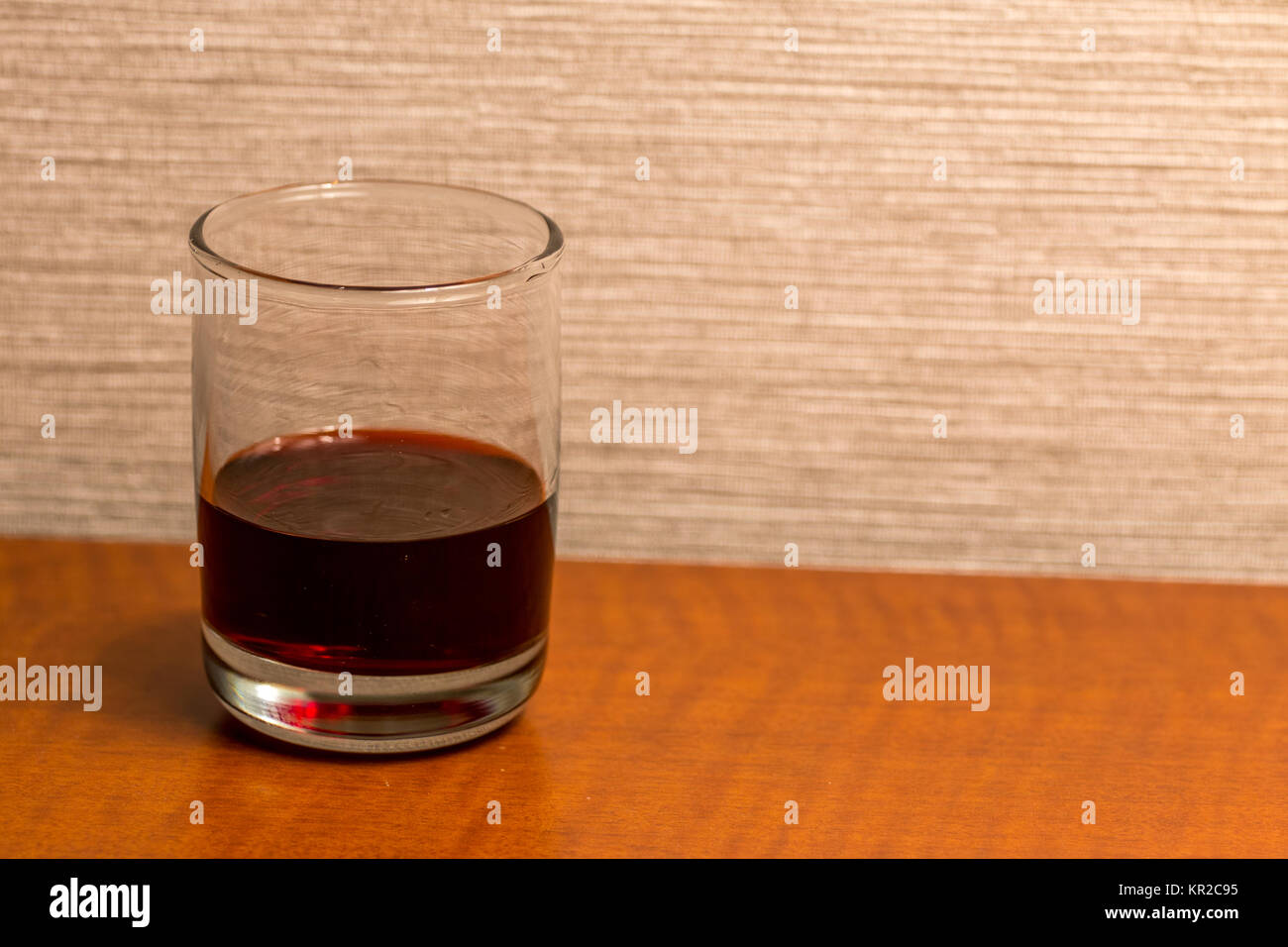 Glass of Red Liquid on Wood Table - Stock Image