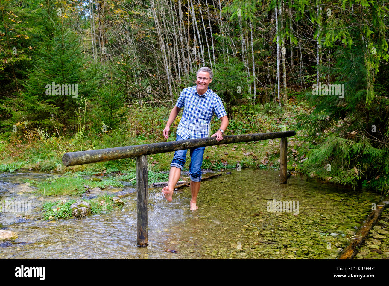 Kneipp man, barefoot in the water Kneipp cure at Schmelzerbach, Inzell, Chiemgau, Upper Bavaria, Bavaria, Germany - Stock Image