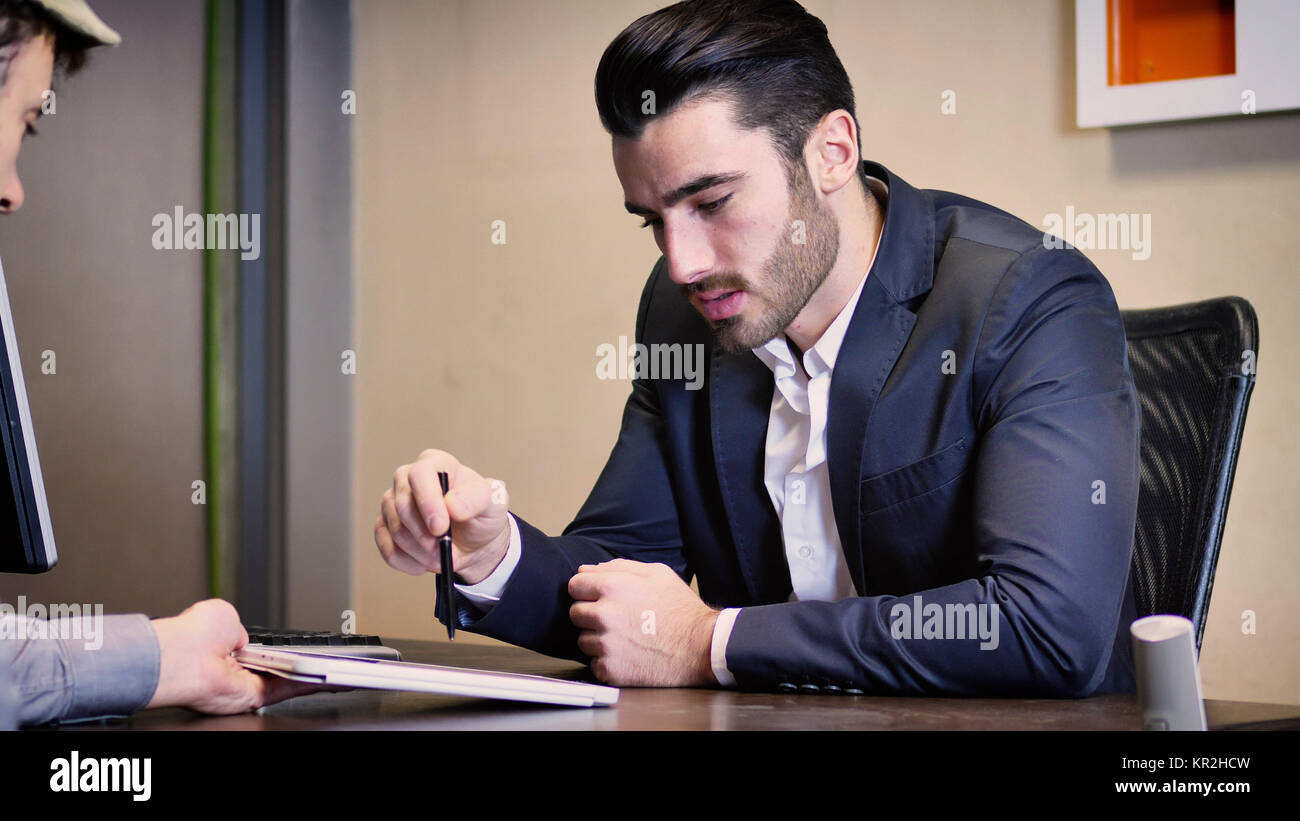Businessman pointing at tablet PC - Stock Image