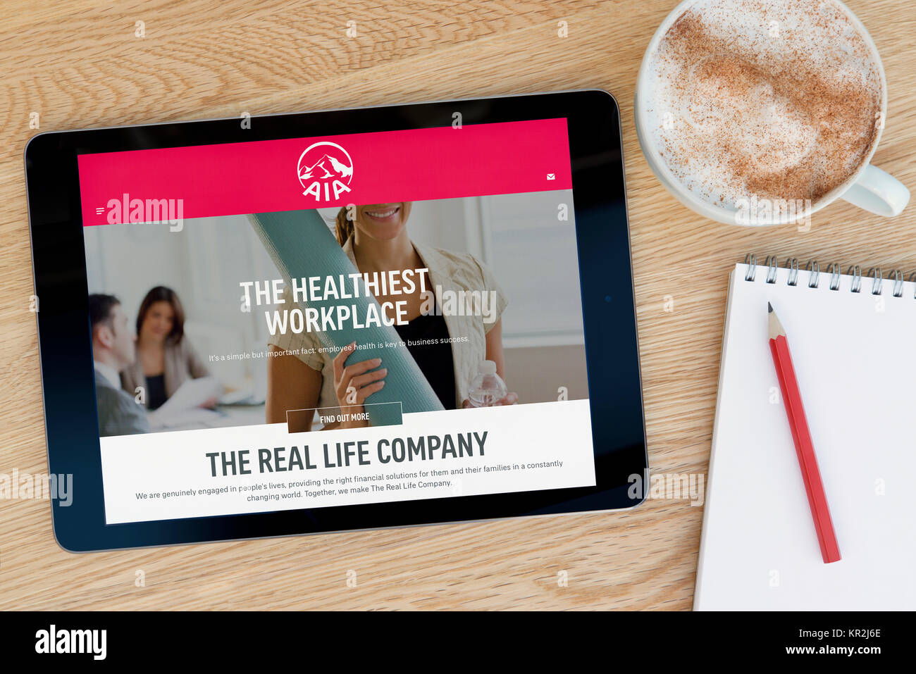 The AIA Group website on an iPad tablet device which rests on a wooden table beside a notepad and pencil and a cup - Stock Image