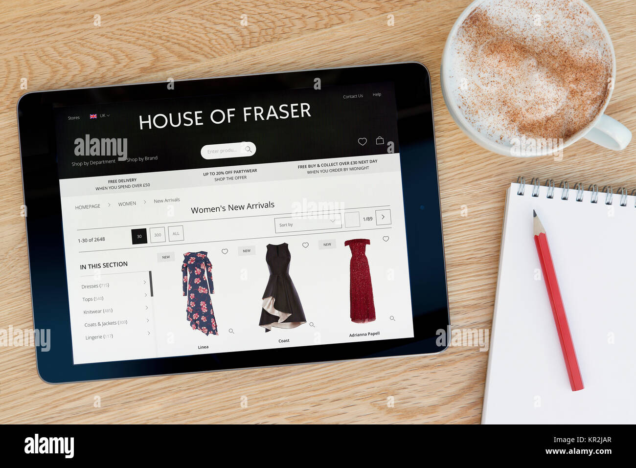The House of Fraser website on an iPad tablet device which rests on a wooden table beside a notepad and pencil and - Stock Image