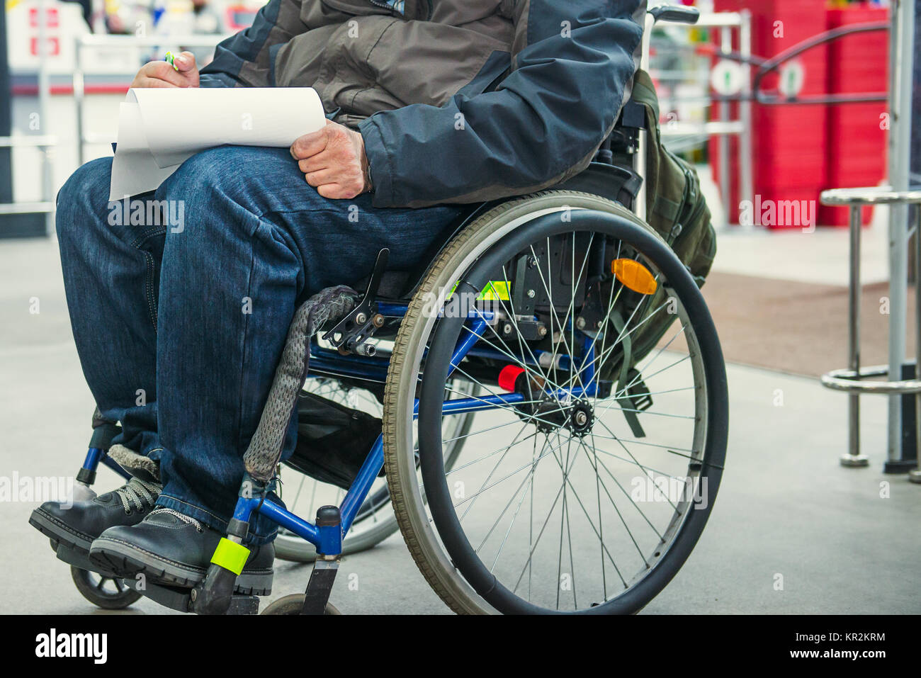 No face disabled, handicapped person on wheeled chair fills the form blank or makes a shopping list in the market Stock Photo