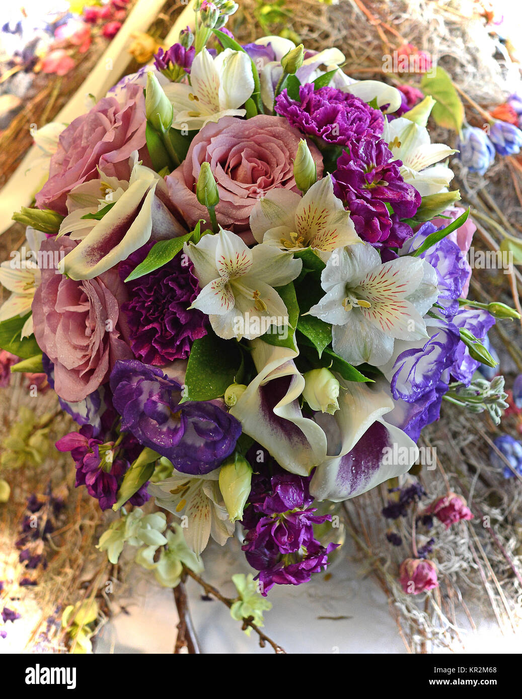 Photo of a colorful nosegay bridal bouquet stuffed with purple calla lilies, rose Lisianthus, pink roses, alstroemeria, - Stock Image