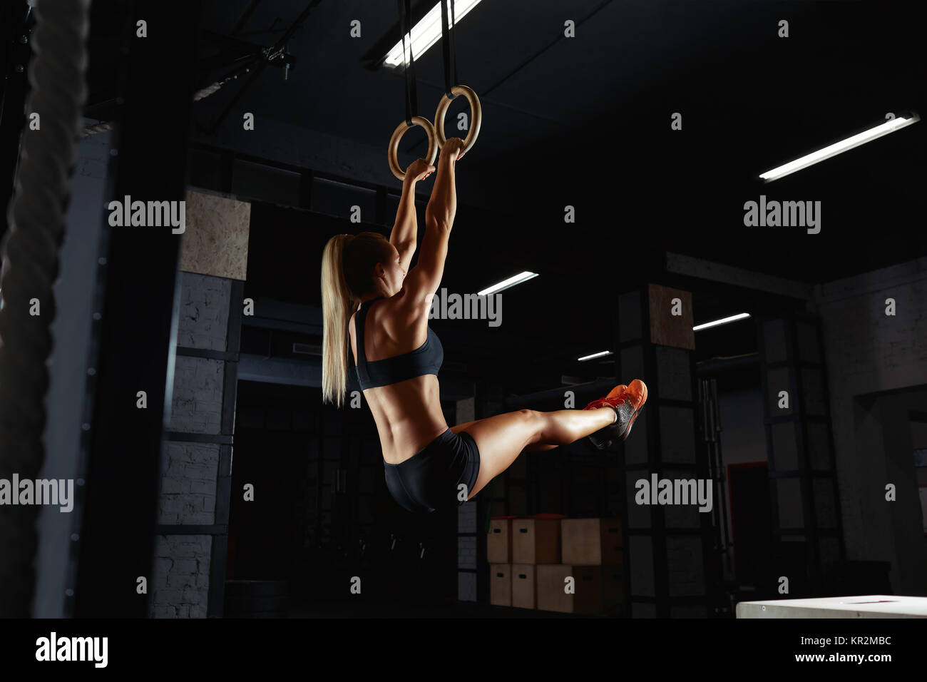 Athletic woman in sports top and shorts working out on gymnastic rings at the gym sportswear equipment strength - Stock Image