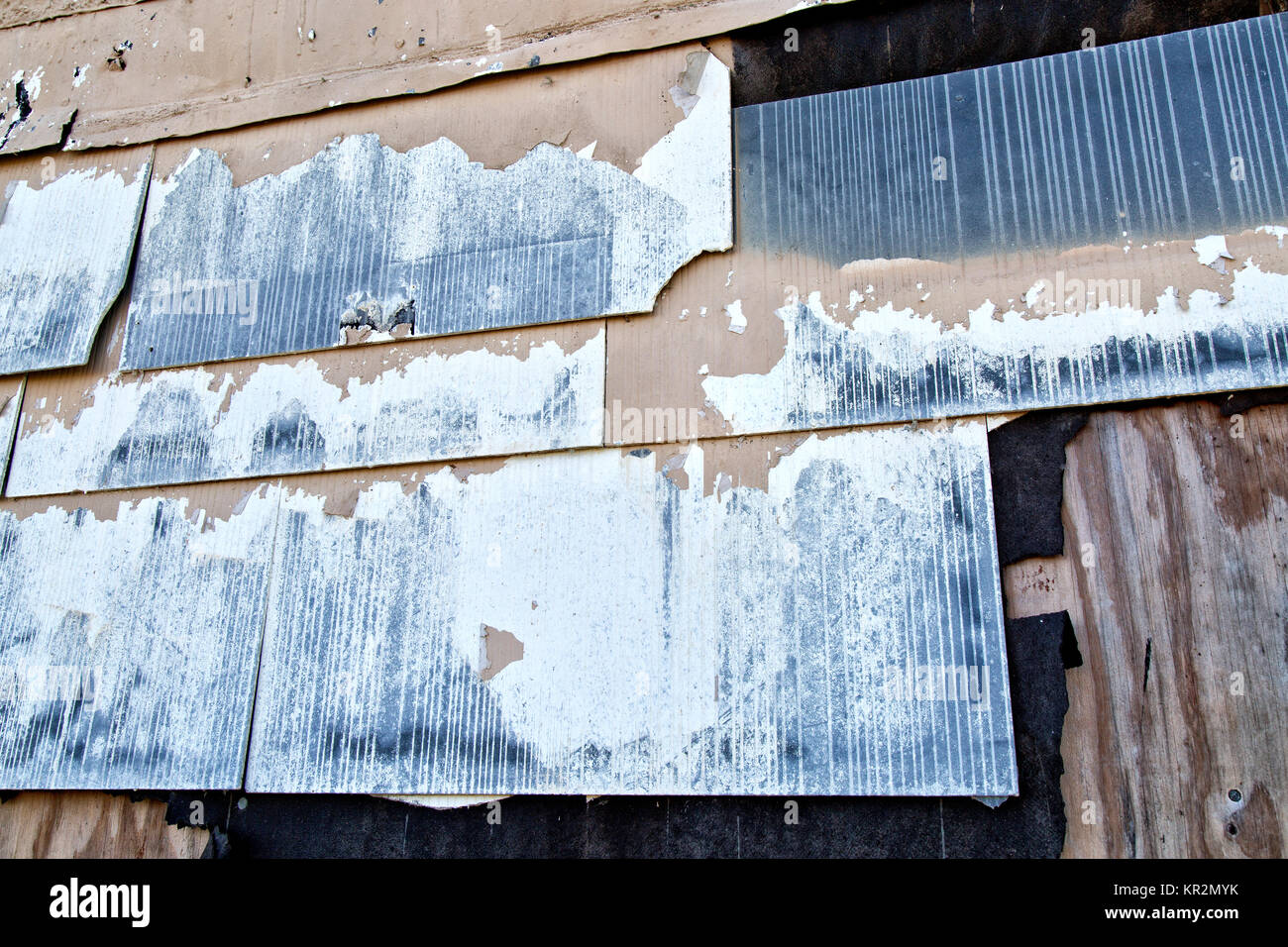 Old asbestos shingle siding attached to exterior structure wall. - Stock Image